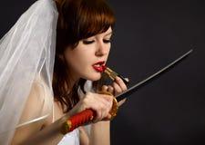 губная помада девушки лезвия смотря шпагу Стоковое Изображение