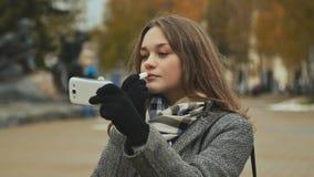 Губная помада молодой красивой губной помады девушки гигиеническая на улице города Осень холодно стоковая фотография