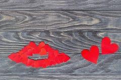 Губы маленьких красных сердец на деревянной предпосылке Концепция  Стоковое фото RF