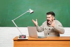 Гувернер Молодой учитель около доски в классе школы o Бородатый учитель в классе образования близко стоковое изображение