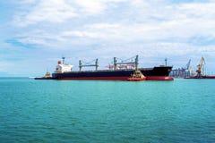 2 гужа причаливают судно-сухогруз на морском порте Черное зачаливание грузового корабля на порте Транспорт груза водой Стоковые Фотографии RF