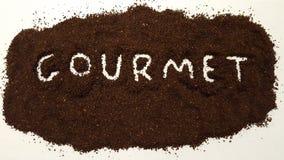 Гурман сказал выход по буквам в земном кофе на белой предпосылке Кофе лакомки стоковое фото