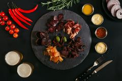 гурман сортировал мясо на доске шифера, различных соусах, овощах и стеклах пива на черноте Стоковые Фото