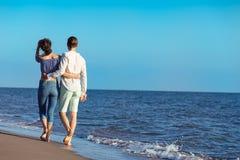 гулять пар пляжа Молодые счастливые межрасовые пары идя на пляж Стоковые Изображения RF