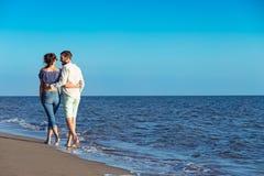 гулять пар пляжа Молодые счастливые межрасовые пары идя на пляж Стоковые Изображения