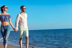 гулять пар пляжа Молодые счастливые межрасовые пары идя на пляж Стоковая Фотография RF