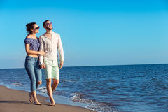 гулять пар пляжа Молодые счастливые межрасовые пары идя на пляж Стоковые Фото