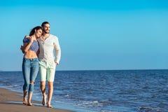 гулять пар пляжа Молодые счастливые межрасовые пары идя на пляж Стоковое фото RF