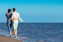 гулять пар пляжа Молодые счастливые межрасовые пары идя на пляж Стоковая Фотография