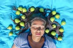 Глаза молодой женщины лежа закрыли груши в черных волосах Стоковое Изображение RF