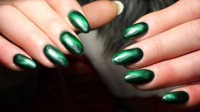 Глаз ` s кота зеленого цвета дизайна ногтя маникюра с неимоверным пирофакелом Стоковая Фотография