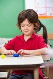 Глина прессформы мальчика на столе Стоковое фото RF