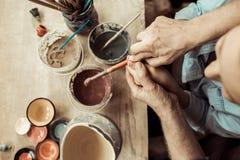 Глиняный горшок и деды картины девушки помогая на мастерской стоковые изображения
