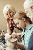 Глиняный горшок и деды картины девушки помогая на мастерской стоковые фото