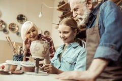 Глиняный горшок и деды картины девушки помогая на мастерской стоковая фотография