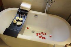 Глиняный кувшин ванны поставленный точки с лепестками Стоковое Фото