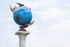 Глобус земли с голубями вокруг его Стоковое Изображение