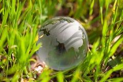 Глобус кристаллического стекла в зеленой траве Стоковое Изображение