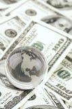 Глобус на куче долларов Стоковое Фото