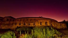 Глубоко - фиолетовый заход солнца за каменным зданием Стоковое Фото