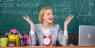 Давно пора учитель с будильником на классн классном Время задняя школа к День учителей Исследование и образование самомоднейше стоковое фото