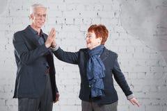 Дайте высокие 5 Счастливые усмехаясь старые пары стоя прижиматься совместно изолированный на белой предпосылке кирпича скопируйте Стоковое Изображение RF