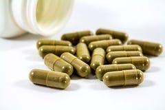 Дайте наркотики, расслоины капсулы травы из бутылки на белой предпосылке, селективном фокусе Стоковые Изображения RF