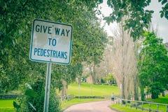 Дайте пешеход-знак пути показывая в парке Стоковые Изображения