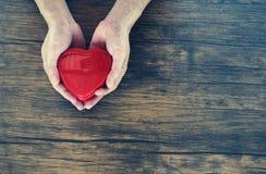 Дайте человека любов держа красное сердце в руках на день Святого Валентина любов подарите помощь дайте тепло любов примите конце стоковые фотографии rf