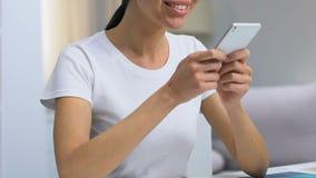 Дама беседуя по телефону с другом и усмехаясь, приятное сообщение, устройство видеоматериал