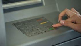 Дама входя в секретный номер для проверки банковского счета и для того чтобы разделить деньги от ATM стоковая фотография