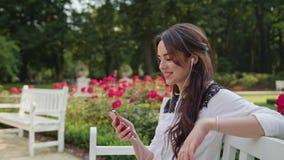 Дама в парке слушая к музыке на телефоне стоковое изображение rf