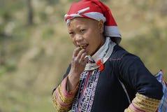 Дама в традиционном красном платье племени холма Dzao ест плодоовощ в Sapa, Вьетнаме Стоковое Изображение RF