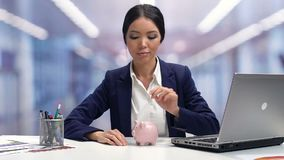 Дама в businesswear кладя монетку в piggybank, сбережения на будущее, банковский взнос видеоматериал