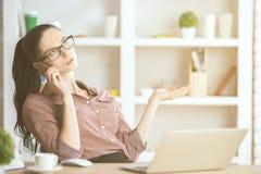 Дама говоря на телефоне на рабочем месте Стоковые Изображения