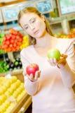 Дама держа красное яблоко в одной руке и зеленое яблоко в другом Стоковая Фотография