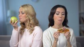 Дама есть пиццу пока женский друг наслаждаясь зеленым яблоком, выбором здорового питания сток-видео