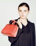 Дама дела моды детенышей довольно холодные нося черный костюм и оранжевый меньшая сумка усмехаясь на белой предпосылке, образе жи Стоковое фото RF