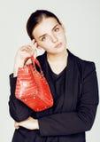 Дама дела моды детенышей довольно холодные нося черный костюм и оранжевый меньшая сумка усмехаясь на белой предпосылке, образе жи Стоковое Изображение RF