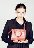Дама дела моды детенышей довольно холодные нося черный костюм и оранжевый меньшая сумка усмехаясь на белой предпосылке, образе жи Стоковое Изображение