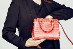 Дама дела моды детенышей довольно холодные нося черный костюм и оранжевый меньшая сумка усмехаясь на белой предпосылке, образе жи Стоковая Фотография RF