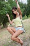 Дама имея потеху на качаниях на парке Стоковые Фотографии RF