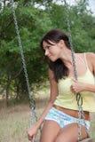Дама имея потеху на качаниях на парке Стоковые Изображения