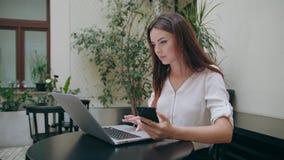 Дама используя компьтер-книжку и телефон в комнате glitch сток-видео