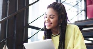 Дама крупного плана очень довольно молодая африканская работая на ноутбуке, на деловом центре, ей сидя на лестницах, и a видеоматериал