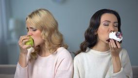 Дама наслаждаясь тортом, женским другом есть яблоко, индивидуальный выбор свойственной еды сток-видео