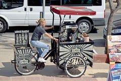 Дама на велосипеде катят 3, который продавая напитки стоковая фотография