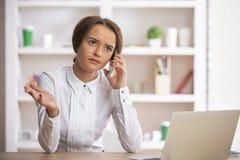 Дама на рабочем месте говоря на smartphone Стоковые Фотографии RF