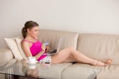 Дама на товарах софы покупая онлайн с кредитной карточкой Стоковое фото RF