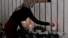 Дама освещает свечи Тепло и атмосфера зимних отдыхов xmas путя украшения клиппирования изолированный оленями красный Новый Год ро видеоматериал